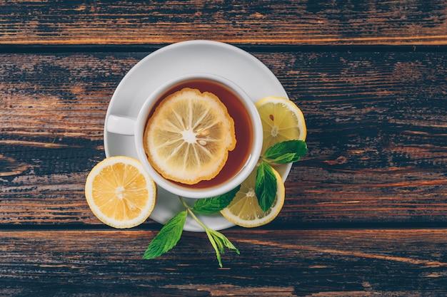 Set di limone e una tazza di tè su uno sfondo di legno scuro. disteso. spazio per il testo