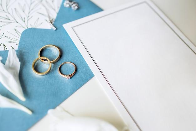 Set di lusso di partecipazioni di nozze, fedi nuziali, accessori eleganti della sposa su uno sfondo bianco.