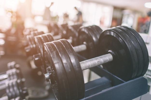 Set di manubri neri. chiuda in su molti manubri nel centro fitness sport. righe in palestra con contrasto hign e colore tono sport e concetto di salute.