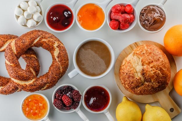Set di marmellate, lamponi, zucchero, cioccolato in tazze, bagel turco, pane, arancia e limoni e una tazza di caffè su una superficie bianca