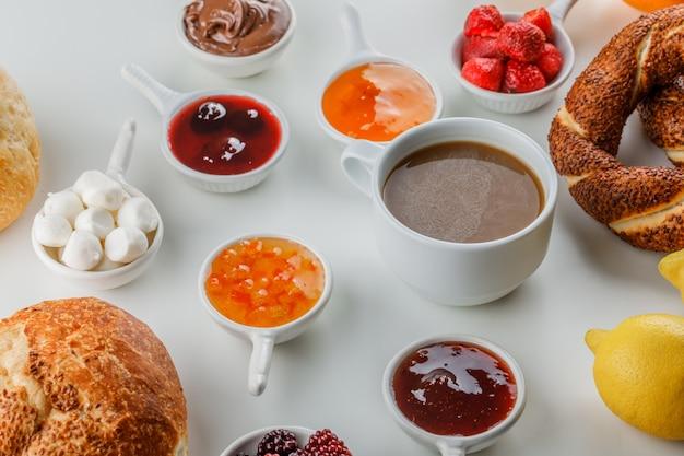 Set di marmellate, lamponi, zucchero, cioccolato in tazze, bagel turco, pane, limone e una tazza di caffè su una superficie bianca