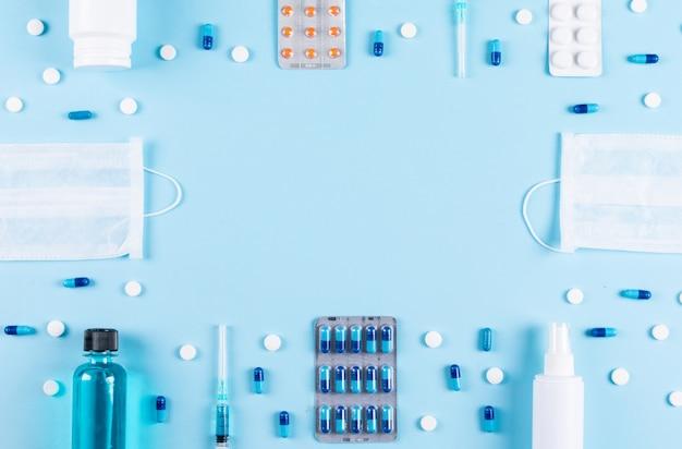 Set di maschere, spray, bottiglia di pillola, aghi e pillole sparsi su uno sfondo ciano chiaro. vista dall'alto. spazio per il testo