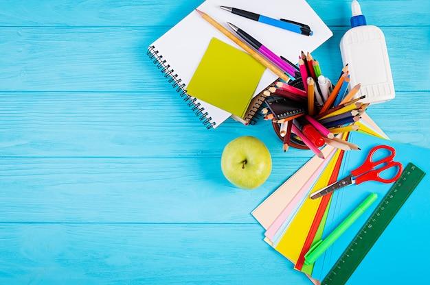 Set di materiale scolastico colorato, libri e quaderni. accessori di cancelleria. vista dall'alto.