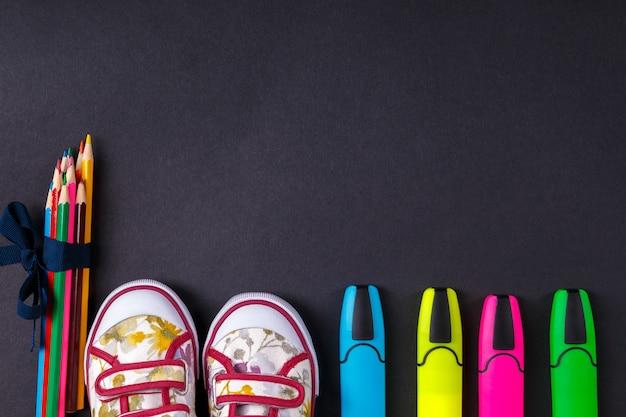 Set di matite colorate avvolte in un nastro blu vicino a scarpe da ginnastica e pennarello
