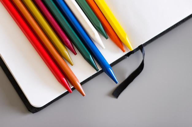 Set di matite colorate con quaderno bianco aperto