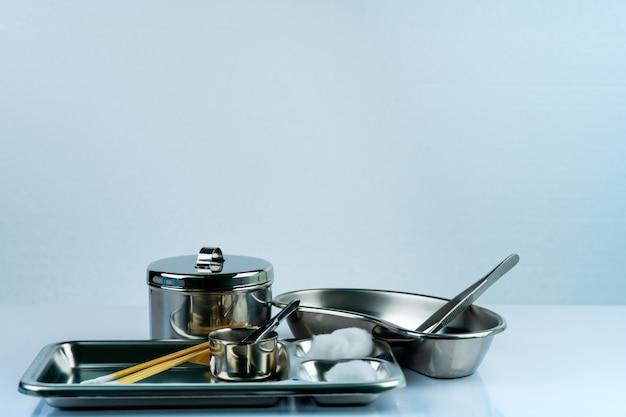 Set di medicazione per ferite e piastra in acciaio inossidabile, pinza, batuffoli di cotone, tazza di iodio, bendaggio conforme, contenitore per strumenti. fornitura medica condimento impostato su sfondo bianco