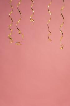 Set di nastri appesi curling appesi su uno sfondo rosa corallo. elementi di decorazioni natalizie. vari serpentine o stelle filanti liberano spazio di testo.