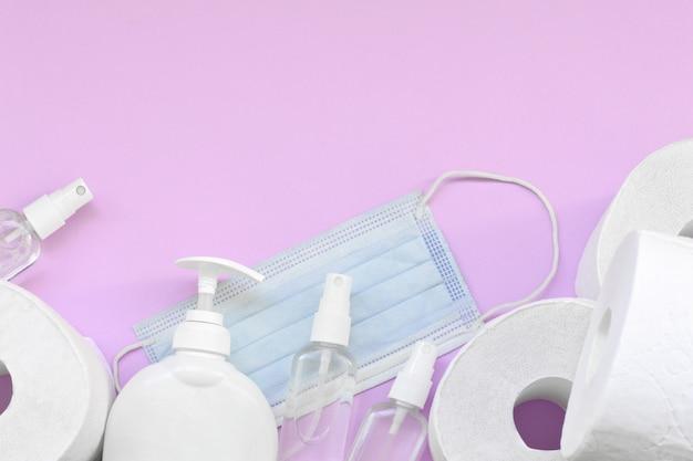 Set di oggetti importanti per i tempi di quarantena covid-19. carta igienica con mascherina chirurgica e disinfettante per le mani con bottiglia di sapone liquido su sfondo lilla