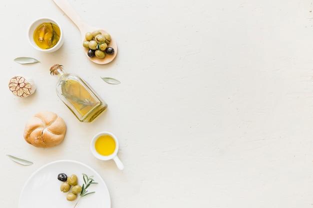 Set di olio bottiglia pane e olive in cucchiaio