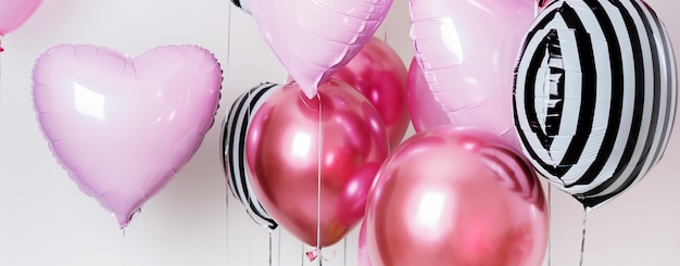 Set di palloncini a forma di cuore e tondo rosa e strisce su sfondo chiaro con spazio di copia.