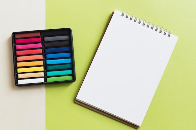 Set di pastello vicino sketchbook