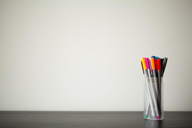 Set di pennarelli in un bicchiere di plastica sul tavolo di legno.