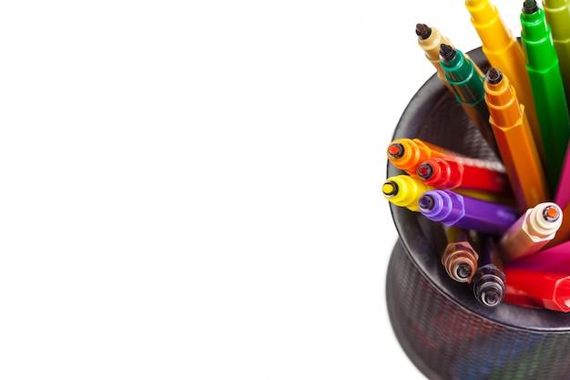 Set di pennarelli in una tazza e un pezzo di carta su bianco