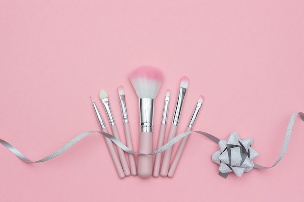 Set di pennelli per il trucco e serpentino a nastro argento con fiocco su rosa pastello
