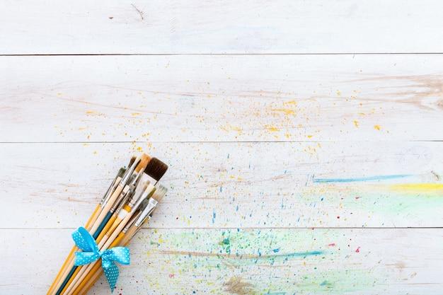 Set di pennelli sul tavolo macchiato dipinto di legno bianco con spruzzi, sfondo di tela artistica, spazio creativo per la pittura, posto di lavoro del pittore, scrivania per bambini per bambini, vista dall'alto con spazio di copia