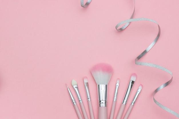 Set di pennelli trucco e serpentino nastro d'argento su sfondo rosa pastello