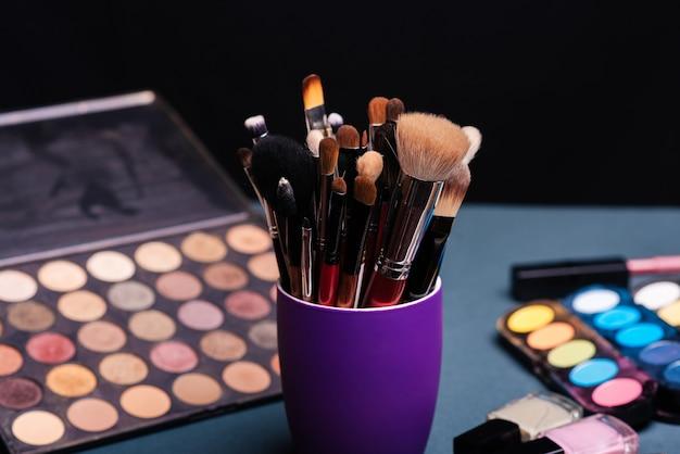 Set di pennelli trucco professionale con una tavolozza con ombretti colorati e cosmetici