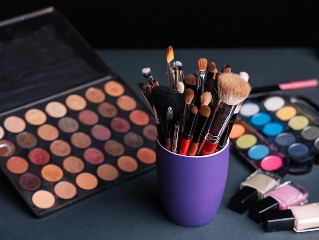Set di pennelli trucco professionale sullo sfondo di una tavolozza con ombretti colorati e cosmetici
