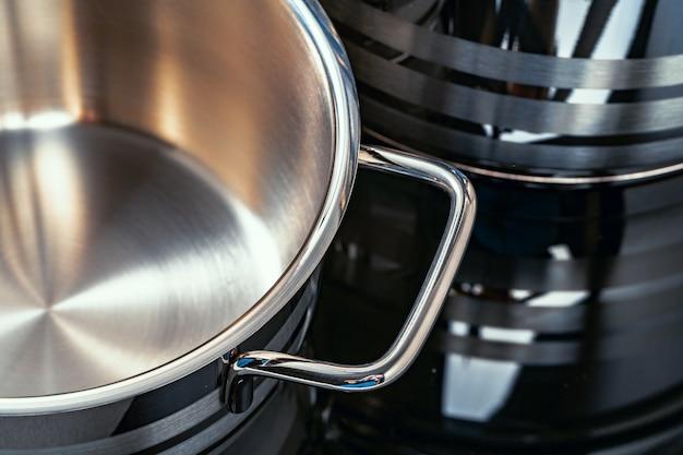 Set di pentole in alluminio sulla superficie nera si chiuda