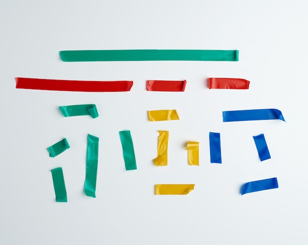 Set di pezzi di gomma multicolori strappati di nastro isolante incollati su una superficie bianca