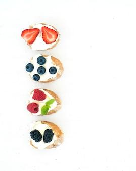 Set di piccoli panini dolci con crema di formaggio e frutti di bosco freschi