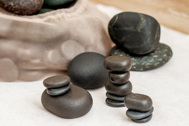 Set di pile di pietre calde di massaggio su un asciugamano in spa.