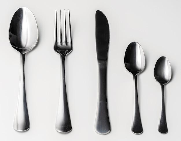 Set di posate d'argento su sfondo bianco