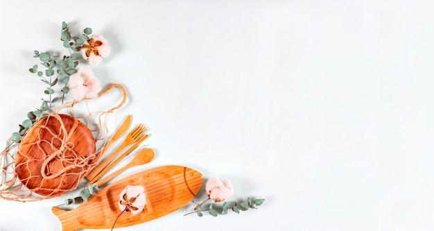 Set di posate in legno naturale eco, piatto, rete a sacco, foglie di eucalipto e fiori di cotone su fondo pastello.