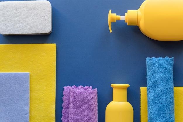 Set di pulizia colorato per diverse superfici su sfondo blu. concetto di pulizia con materiali di consumo bottiglie di plastica, contenitori di detersivo, panno in microfibra, spugna, straccio e detergente, copia dello spazio
