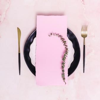 Set di ramoscello secco e carta sul piatto vicino a posate