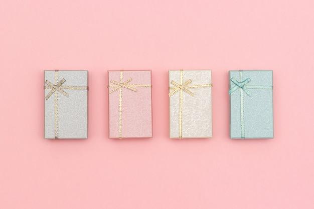 Set di scatole regalo di colori pastello su sfondo rosa, vista dall'alto