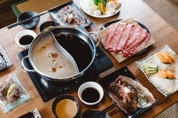 Set di shabu tra cui fette rari di manzo wagyu a5, shabu shoyu e base trasparente, salmone, sushi.