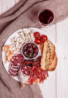 Set di snack al vino. varietà di formaggio e carne, olive, pomodori su fondo bianco