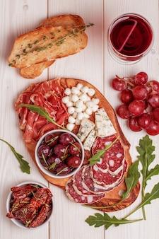 Set di snack al vino. varietà di formaggio e carne, olive, uva, rucola su fondo bianco