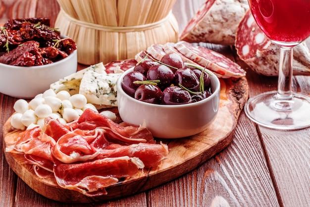 Set di snack al vino. varietà di formaggio e carne su sfondo scuro.