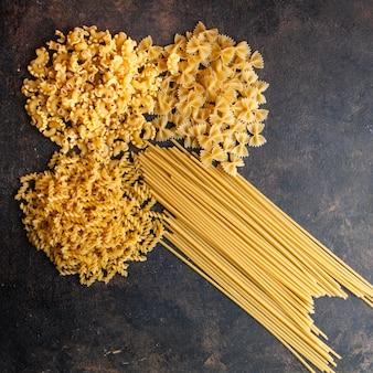 Set di spaghetti e maccheroni di pasta su uno sfondo scuro con texture. vista dall'alto.