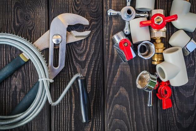 Set di strumenti e pezzi di ricambio per idraulici su tavole scure vintage