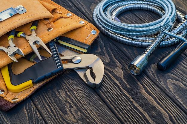 Set di strumenti nella borsa per idraulici su assi di legno vintage scuri