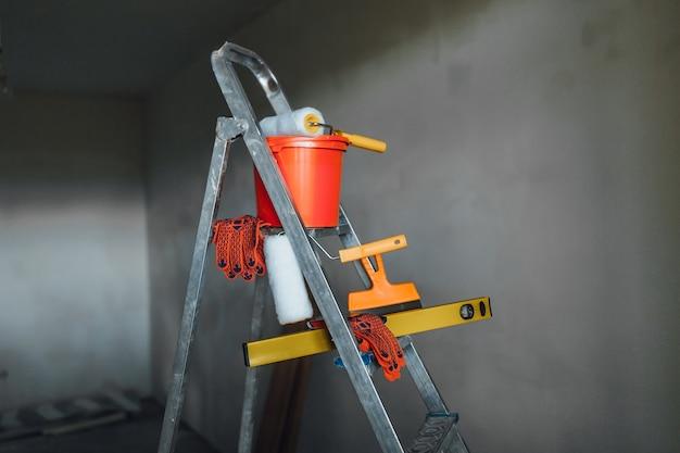 Set di strumenti per la riparazione con pittore offuscata su appartamento grigio
