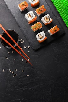 Set di sushi e maki sul tavolo di pietra. vista dall'alto con spazio di copia