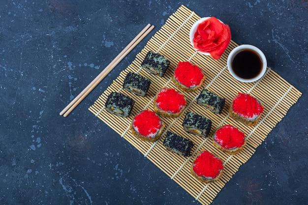 Set di sushi roll con frittata, tofu e verdure, uova di pesce volante, tempura su makisu. cibo tradizionale giapponese.