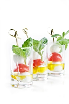 Set di tartine in vetro con insalata di mozarella, pomodoro e olio d'oliva in grecia
