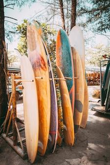 Set di tavole da surf colorati differenti in una pila disponibile per l'affitto sulla spiaggia.