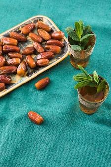 Set di tazze con ramoscelli di piante e frutta secca sul vassoio