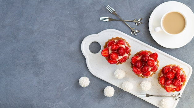Set di tortine di fragole o mini torte di bacche con una tazza di caffè e caramelle. vista del piano d'appoggio del dessert di estate