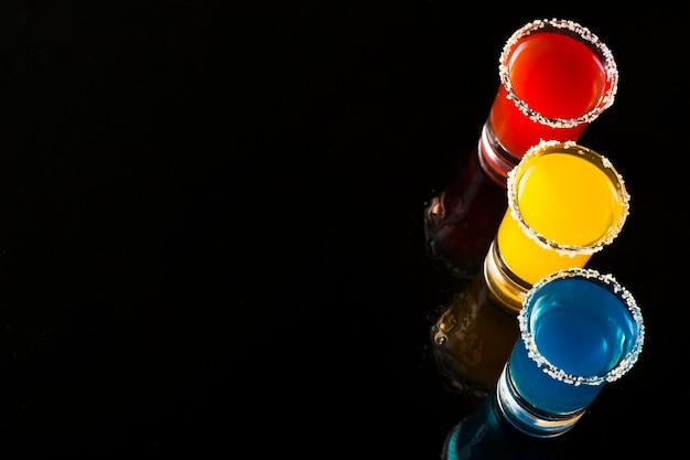 Set di tre bicchierini colorati con cocktail e copia spazio