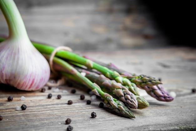 Set di un mazzo di asparagi e aglio su un fondo di legno scuro. avvicinamento.