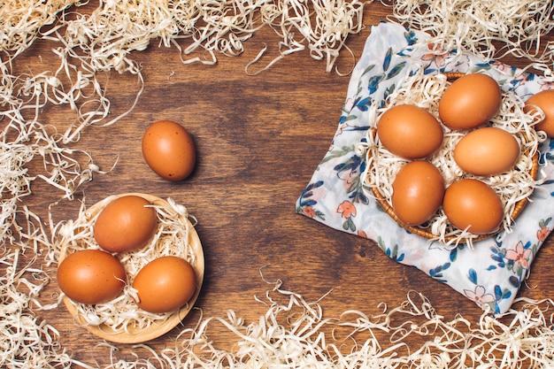 Set di uova di gallina in ciotole su materiale fiorito tra orpelli a bordo