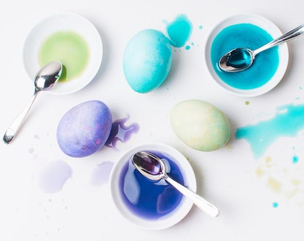 Set di uova di pasqua colorate tra macchie, cucchiai e liquido di tintura in piattini