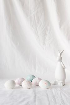 Set di uova di pasqua con disegni vicino a figura di coniglio